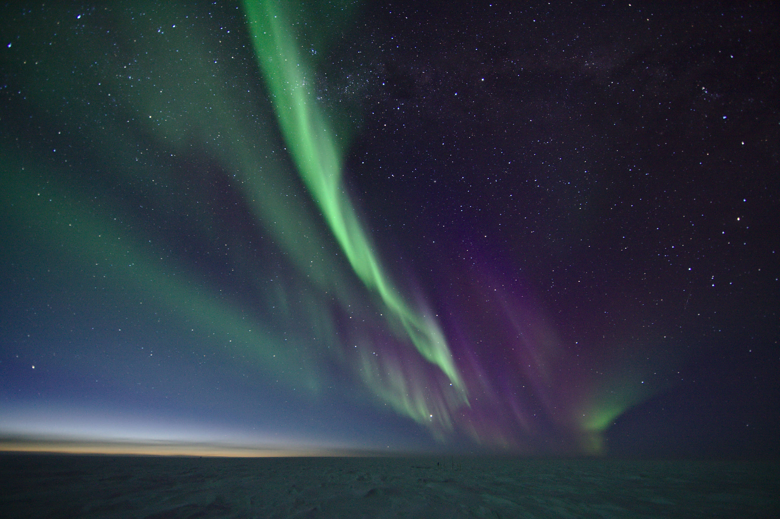 View outside - the frozen landscape of the south pole illuminated by beautiful auroras and a tiny glimpse of sunlight