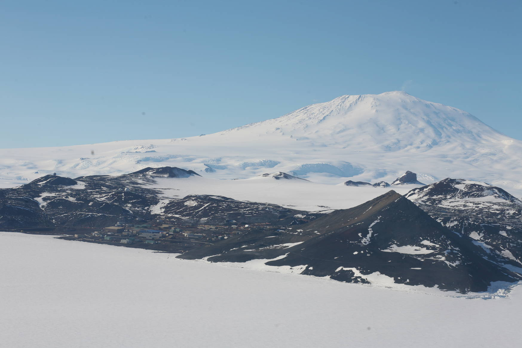 A first view of the McMurdo base: the white mountain in the background is the active volcano Erebus. The hill to the front right is the 'Observation hill'.