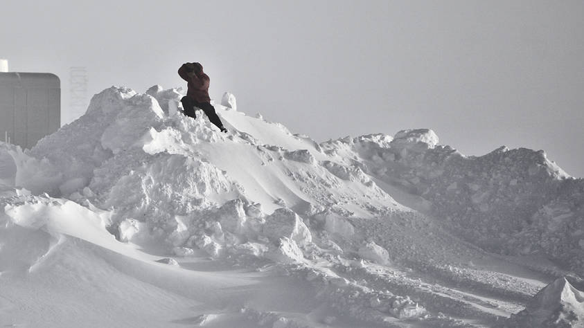 A photographer climbing a snow hill to get a good angle of the arriving aircraft